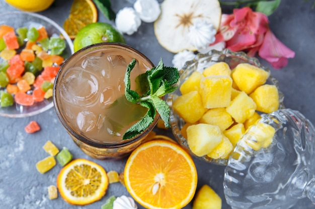 Cold refreshing pineapple cocktail with lime and mint for a hot summer day on a gray background decorated with candied fruit, mint and pineapple cubes. mojito idea, homemade lemonade with ice cubes.
