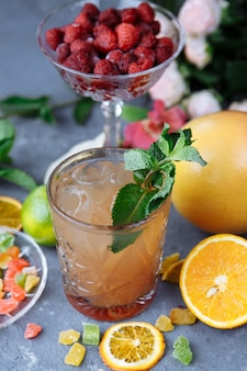 Cold refreshing pineapple cocktail with lime and mint for a hot summer day on a gray background decorated with candied fruit, mint and pineapple cubes.