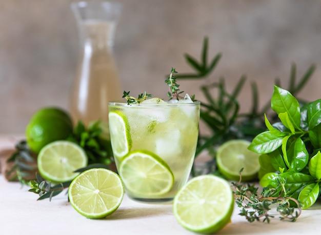 Холодный освежающий летний напиток или лимонад с лаймом и тимьяном на бетонном фоне. выборочный фокус.