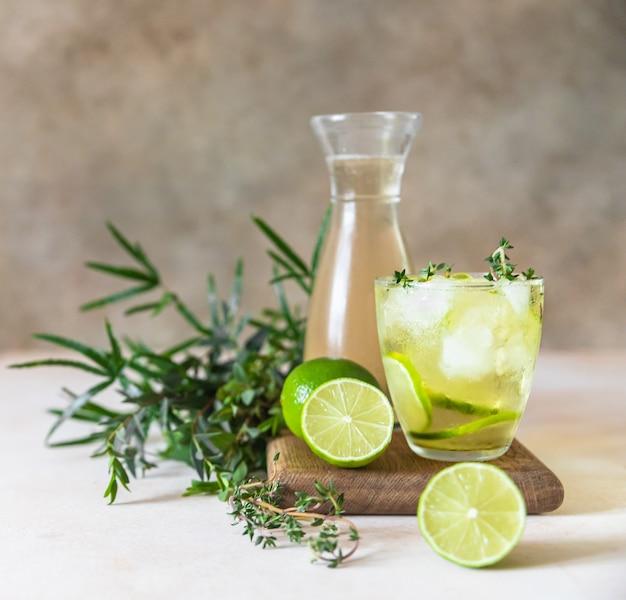 Холодный освежающий летний напиток или лимонад с лаймом и тимьяном на бетонной поверхности