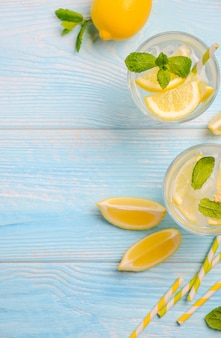 Cold refreshing summer drink with lemon and mint on light blue wooden background