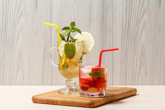 Холодный освежающий летний лимонад мохито с дольками лимона и мятой в высоком стакане и клубничный лимонад с мятой в коротком на деревянной разделочной доске