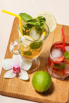 Cold refreshing summer lemonade mojito with lemon slices and mint in a tall glass and strawberry lemonade with mint in a short one on wooden cutting board. top view.