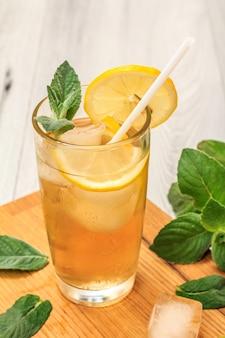 Холодный освежающий летний лимонад со льдом и дольками лимона, украшенный листьями мяты в высоком стакане на разделочной доске и сером деревянном фоне
