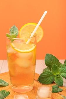 Холодный освежающий летний лимонад со льдом и дольками лимона, украшенный листьями мяты в высоком стакане на разделочной доске