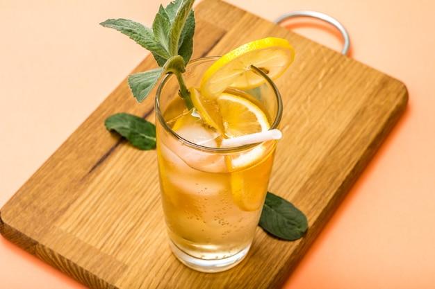 Холодный освежающий летний лимонад со льдом и дольками лимона, украшенный листьями мяты в высоком стакане на деревянной разделочной доске и персиковом фоне
