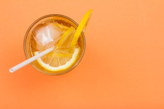 Холодный освежающий летний лимонад со льдом и ломтиками лимона в высоком стакане на фоне персикового цвета с копией пространства. вид сверху