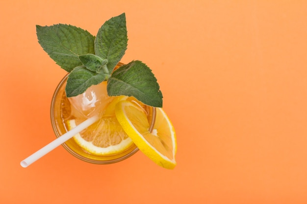Cold refreshing summer lemonade with ice and lemon slices, decorated with mint leaves in a tall glass on peach colored background with copy space. top view