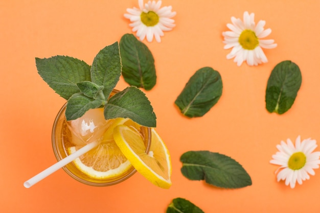 Cold refreshing summer lemonade with ice and lemon slices in a tall glass with mint leaves and chamomile flowers on peach colored background. top view