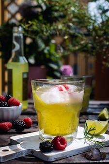 Cold refreshing tarragon, blackberry and raspberry lemonade with ice on wooden rustic table i