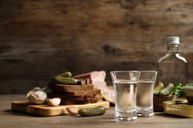 Холодная русская водка с закусками на деревянном столе