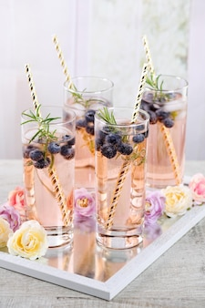 Cold shot in glass with blueberry, ice cubes, rosemary. celebratory inspiration in provence style