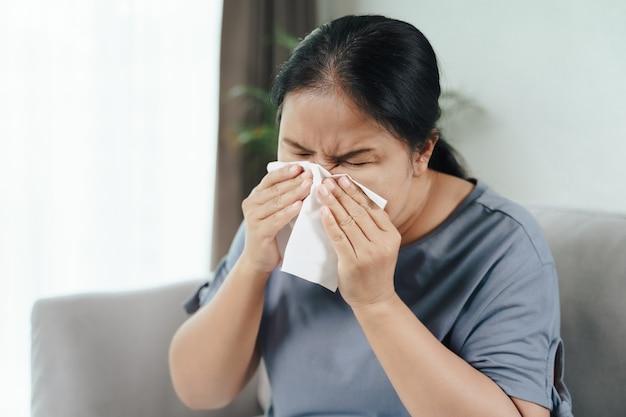 風邪をひいた女性は、ソファにティッシュペーパーを置いて、鼻アレルギーの咳やくしゃみをしました。ヘルスケアと医療の概念。