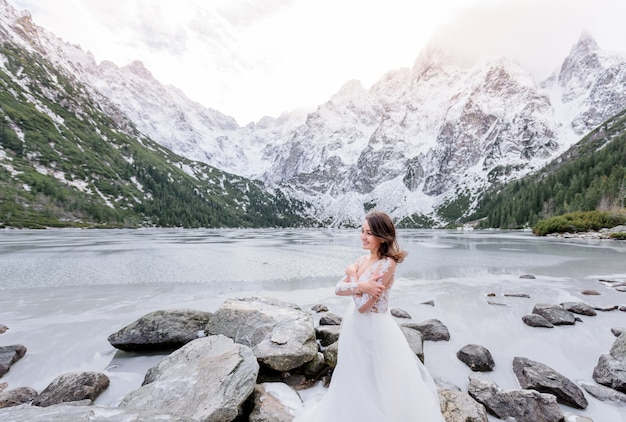 Cold smiled girl dressed in the wedding dress is standing near the frozen highland lake in winter