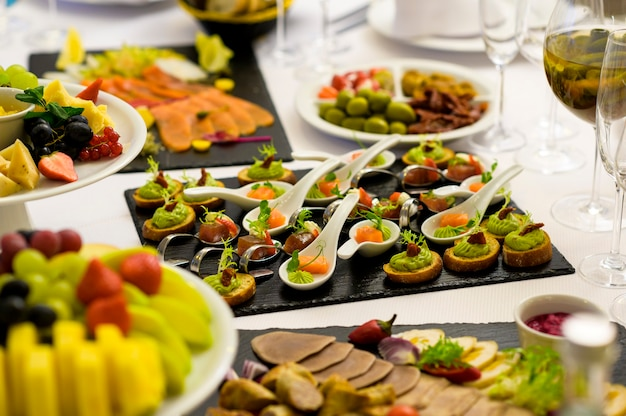 Cold snacks and slices in a restaurant and cafe on a banquet table with delicacies on spoons and in plates
