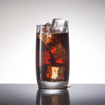 Cold soda with ice in glass closeup