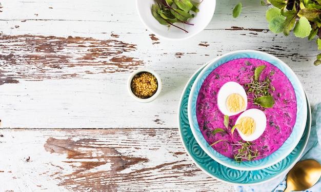 Холодный суп из свеклы, огурцов и украшенный яйцом в синей тарелке на деревянном фоне. вид сверху.