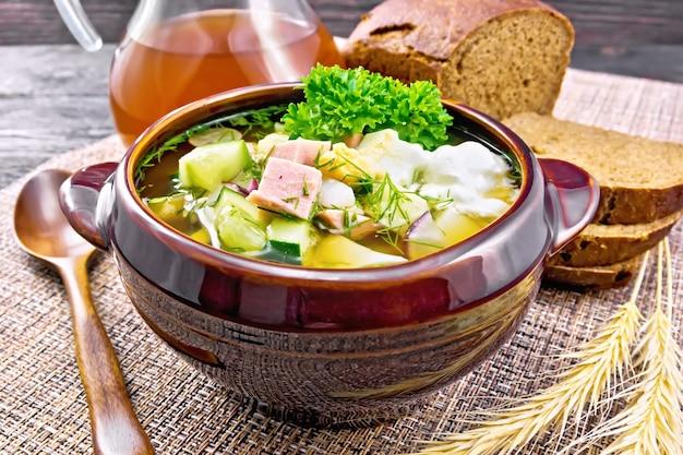 Холодный суп окрошка из колбасы, картофеля, яйца, редиса, огурца, зелени и напитка кваса в глиняной посуде, хлеб на плетеной салфетке на фоне темной деревянной доски