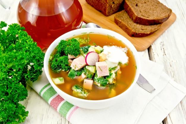 Холодная суповая окрошка из колбасы, картофеля, яиц, редиса, огурца, зелени и кваса в белой миске на салфетке, хлебе и кувшине с напитком на фоне светлой деревянной доски