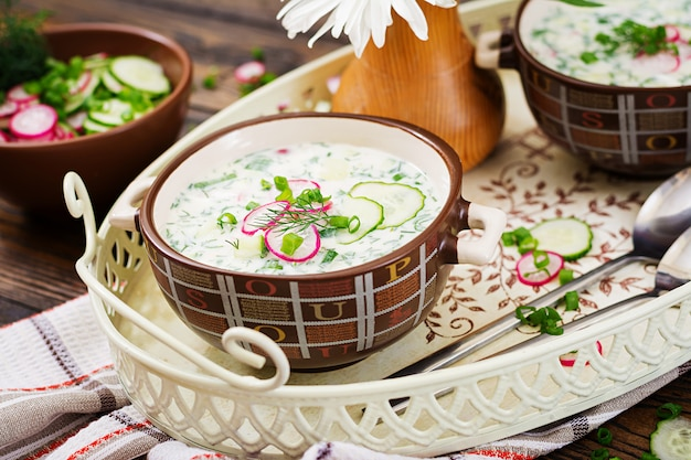Cold soup with fresh cucumbers, radishes with yoghurt in bowl on wooden table. traditional russian food - okroshka. vegetarian meal.