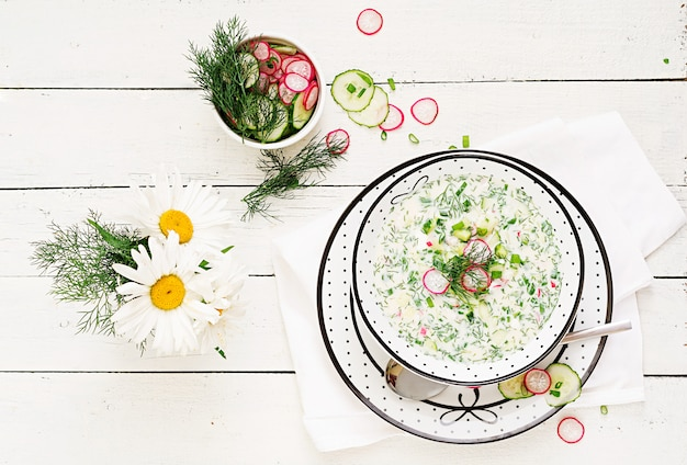 Cold soup with fresh cucumbers, radishes with yoghurt in bowl on wooden table.