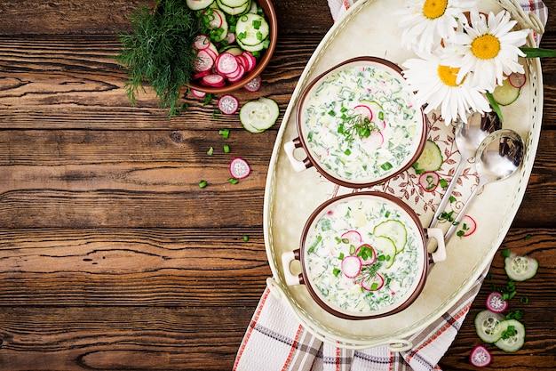 新鮮なキュウリの冷たいスープ、木製の背景上にボウルにヨーグルトと大根。