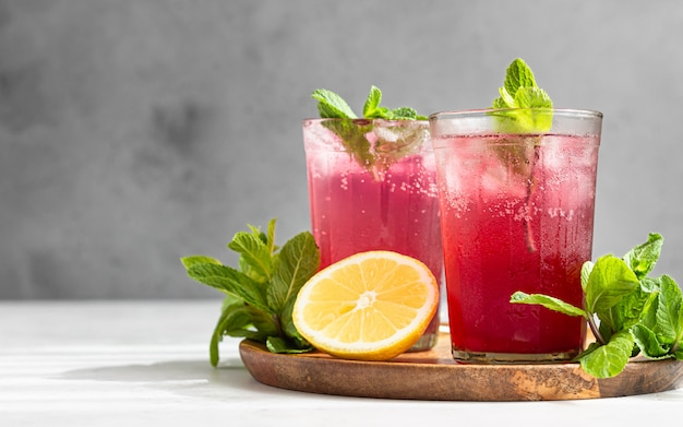 Cold sparkling hibiscus or karkade tea with lemon, mint and ice. summer drink, lemonade.