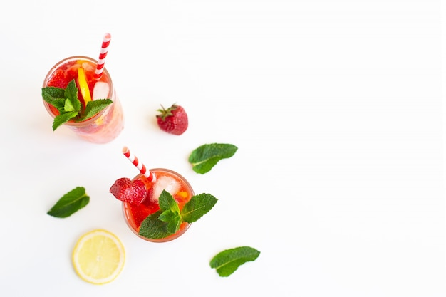 Cold strawberry lemonade juice with ice cubes, mint, lemon, cocktail tube and on white backgraund. cold summer drink.