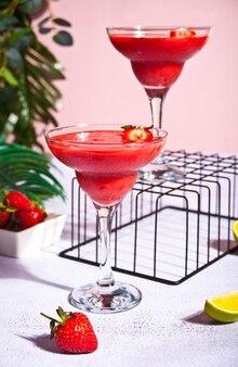 ライムとラム酒のグラスに入った冷たいストロベリー マルガリータまたはダイキリ カクテル