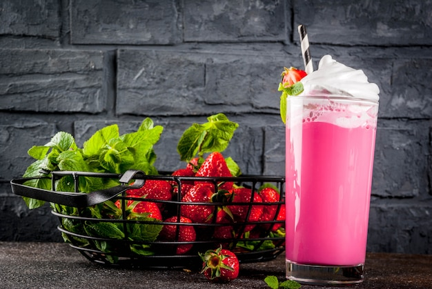 Cold strawberry  milkshake with fresh berries and mint on dark background