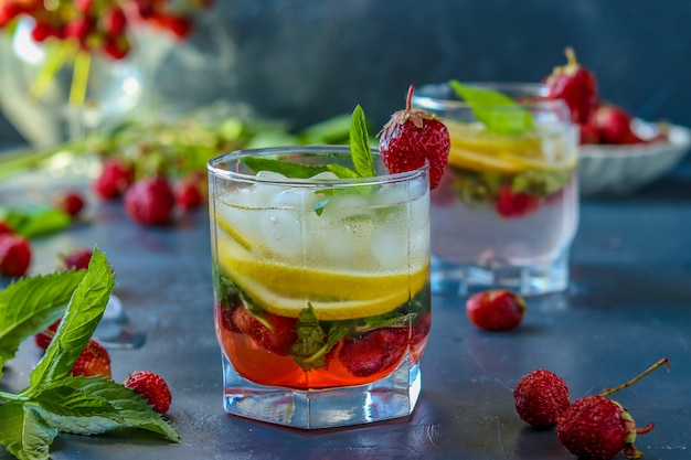 Cold strawberry mojito drink with strawberry, lemon slices and mint