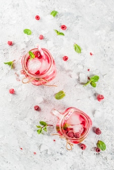 Cold summer drink, raspberry sangria, lemonade or mojito with fresh raspberry and syrup, mint leaves, on grey stone  copyspace top view