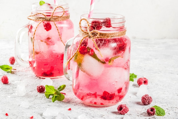 Cold summer drink, raspberry sangria, lemonade or mojito with fresh raspberry and syrup, mint leaves, on grey stone  copyspace