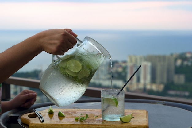 Cold summer drink with lime and mint on a balcony