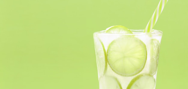 Cold summer drink with lime slices frozen in ice glass