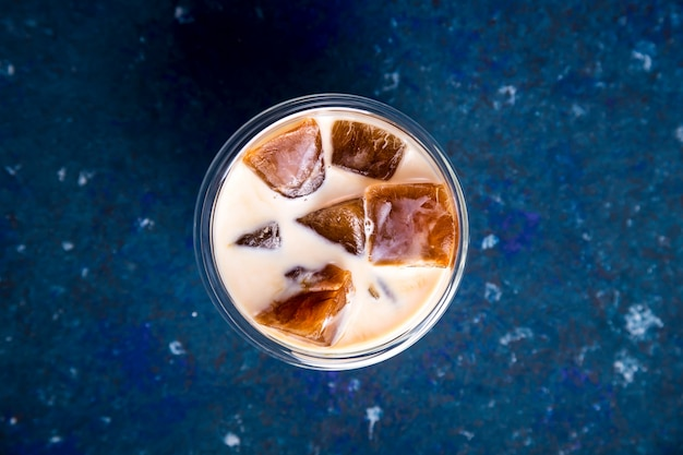 Cold summer refreshing drink with coffee ice and milk on a blue table