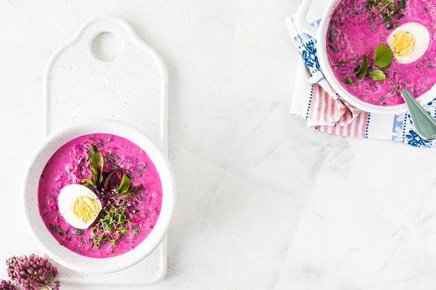 Холодный летний суп из свеклы, огурцов и яиц в белой тарелке на белом каменном столе. вид сверху. скопируйте пространство.