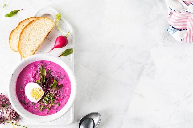 白い石のテーブルの上の白いプレートにビート、キュウリ、卵の冷たい夏のスープ。上面図。スペースをコピーします。