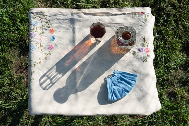 Cold tea and facemask flat lay table in the garden at sunset, top view
