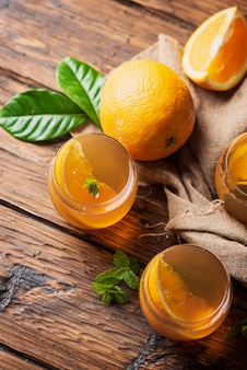 Cold tea with orange and mint on the wooden table, selective focus
