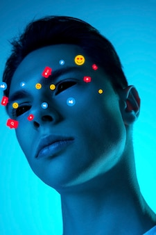 Cold. tears illustrated of social media activity signs on male face in neon light. real life versus online lifestyle, addiction to modern technologies concept. copyspace for ad. creative artwork.