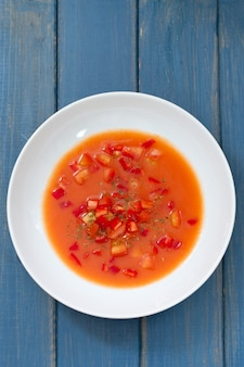 Cold tomato soup in blue wooden surface
