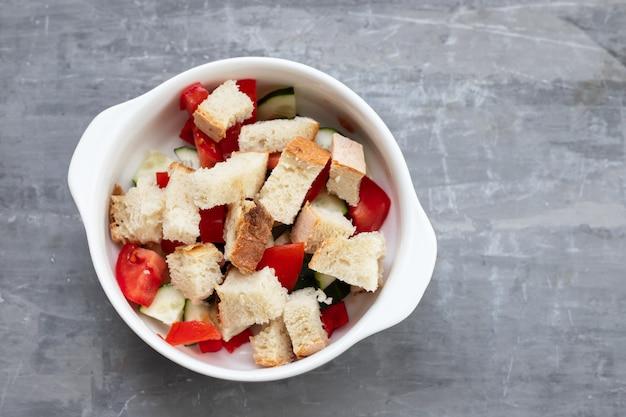 白いボウルにパンと冷たいトマトスープガスパチョ