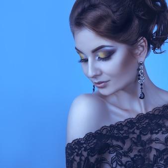 青い壁に優雅な大人の女性の冷たいトーンの肖像画