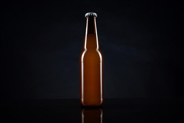 黒い表面にキャップが付いた冷たい未開封のビール瓶。