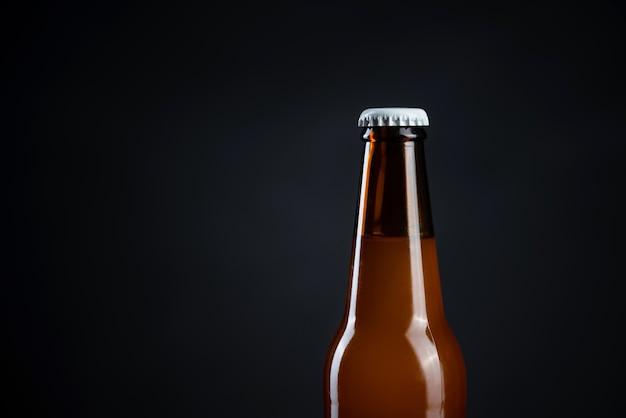 キャップ付きの冷たい未開封のビール瓶。