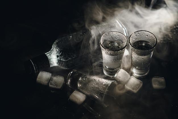 Холодная водка в рюмках на черном фоне. вид сверху. еда фон