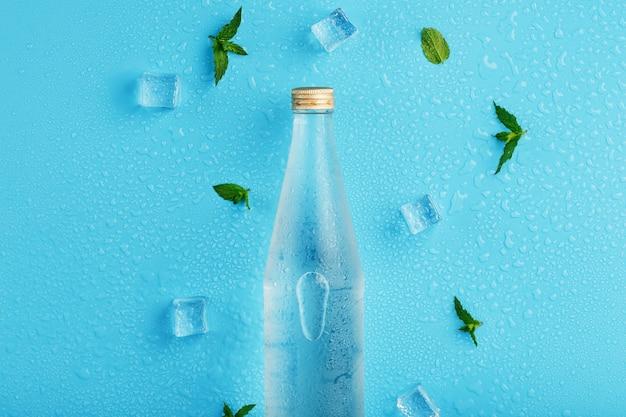 Бутылка холодной воды, кубики льда, капли и листья мяты на синем.