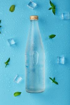 冷たい水ボトル、アイスキューブ、滴、ミントの葉