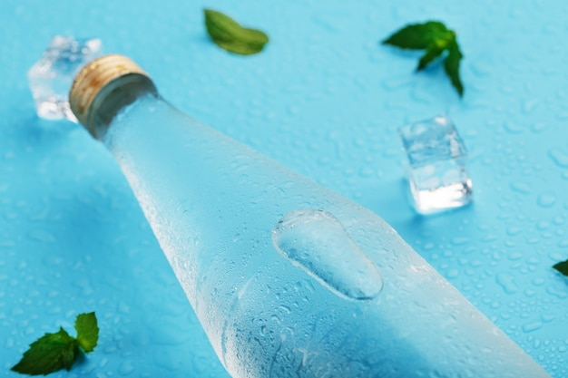 Cold water bottle, ice cubes, drops and mint leaves on blue.